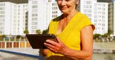 metade do comprimento : Senior woman using digital tablet at promenade on a sunny day 4k