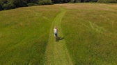 İrlanda : Aerial view of woman riding bicycle in green field 4k Stok Video