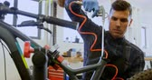 metade do comprimento : Attentive man repairing bicycle in workshop 4k Stock Footage