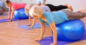 alongamento : Trainer assisting senior women in performing yoga at yoga center 4k