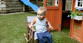 casual sitting : Baby boy playing with chair at backyard 4k