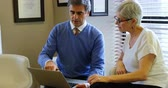 elliler : Optometrist discussing over laptop with patient in clinic 4k