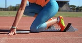 olympic : Side view of female athlete taking starting position on running track 4k Stock Footage