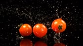 limpeza : Close-up of tomatoes falling on water against black background 4k