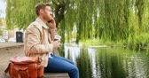 três quarto comprimento : Man having coffee while talking on mobile phone near river 4k