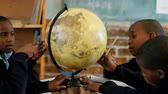 estudioso : Schoolkids using globe in classroom at school 4k Stock Footage