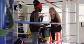 combattente : Female boxer relaxing in boxing ring at fitness studio 4k Filmati Stock