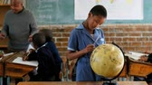 estudioso : Schoolgirl using globe in classroom at school 4k