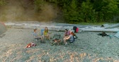 jovens : Panning shot of friends enjoy camping near the forrest. Friends sitting near campfire while playing the guitar.