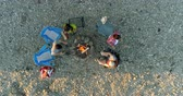 bir kişi : Aerial shot of group of friends standing near campfire. Friends having good time with each other.