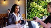 nfc technology : Front view of a young pretty mixed race businesswoman making payment through NFC in a cafe 4k. The well dressed female pay with credit card. Stock Footage