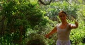 hosszúság : Young ballerina dancing in the park. Dancing gracefully on a sunny day amidst green trees 4k