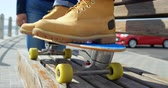 skateboard : Close-up of man sitting on skateboard near beach. Woman standing beside him on a sunny day 4k