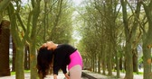 três quarto comprimento : Young ballerina dancing in the park. Tree lined in the background 4k