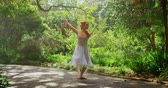 klasik : Young ballerina dancing in the park. Dancing gracefully ona sunny day amidst green trees 4k
