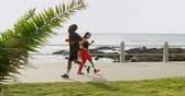 human limb : Couple jogging at promenade on a sunny day. Beautiful sky and calm sea in the background 4k