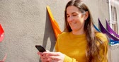 cabeça e ombros : Beautiful woman using mobile phone on a sunny day. Beautiful smiling woman 4k