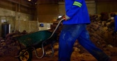 padesátých let : Worker working in foundry workshop. Worker walking with wheel barrow 4k
