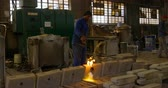 três quarto comprimento : Worker heating metal mold with blow torch in foundry workshop.  Worker working in foundry workshop 4k