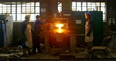 planoucí : Worker pouring molten metal in container. Worker working in foundry workshop 4k
