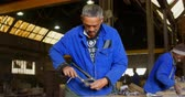 kelepçe : Worker adjusting clamp in foundry workshop. Workers working in the background 4k Stok Video