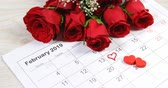 年代測定 : Bouquet of red roses on the calendar showing 14th February. Valentines day concept 4k 動画素材