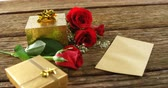 коробка подарка : Red roses, gift boxes and card on a wooden surface. Bouquet of red roses around the gift box 4k