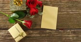 planche de bois : Red roses, gift boxes and card on a wooden surface. Bouquet of red roses around the gift box 4k