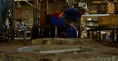 метла : Worker cleaning with broom in foundry workshop. Coworker carrying metal mold 4k