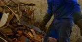 atento : Worker putting metal in wheelbarrow in foundry workshop. Rusted scrap metal pile 4k