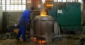 melting of metal : Worker melting metal in furnace at workshop. Worker collecting hot metal 4k