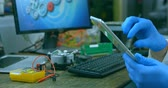 global cooling : Close-up of robotic engineer using digital tablet. Circuit board and tools on desk 4k