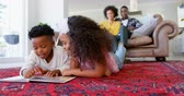 lying on front : Front view of cute black kids reading story book in living room comfortable home. Mother and father relaxing on the couch 4k Stock Footage