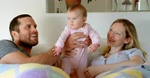 lying on front : Front view of mid adult caucasian parents playing and holding baby on bed in a comfortable home. Family relaxing on bed 4k Stock Footage