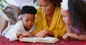 lying on front : Front view of black mother with her children reading a book in a comfortable home. Black mother with her daughter and son relaxing at home 4k