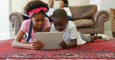 lying on front : Front view of black kids using digital tablet in living room at home. Black mother and father relaxing in the background 4k