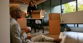 gobelet carton : Side view of young black businessman drinking coffee in modern office. Female coworker unpacking cardboard boxes in the background 4k Vidéos Libres De Droits