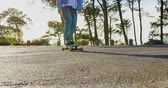 křižník : Front view of young male skateboarder riding on skateboard on country road. Skateboarder skating on skateboard in the sunshine 4k