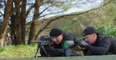 lying on front : Front view of caucasian military soldiers looking through binoculars and riflescope at training. They are lying on ground 4k Stock Footage