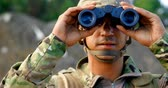 campo de batalha : Front view of young caucasian military soldier observing on field during military training. He is using binocular 4k
