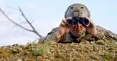 arranque : Front view of military soldier looking through binoculars during military training. Military soldier lying on the ground 4k