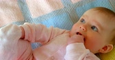 дома : Front view of cute caucasian baby relaxing on baby bed in a comfortable home. Baby chewing fingers and looking away 4k