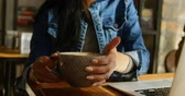 кафетерий : Front view of young Asian woman drinking coffee at table in cafe. Young Asian woman sitting with laptop at table 4k Стоковые видеозаписи