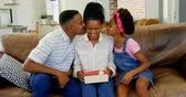 three two one : Front view of black father and daughter kissing woman in living room at home. Black woman holding a gift box 4k Stock Footage