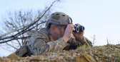 sniper : Side view of military soldier looking through binoculars during military training. Military soldier lying on the ground 4k