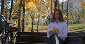 refreshment time : Front view of young Caucasian man having coffee in the park. Carefree man sitting on bench with autumn trees in background 4k Stock Footage