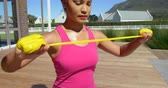 pool deck : Low angle view of young pretty mixed-race woman exercising in backyard of home. She is using resistance band and working out in the sunshine 4k Stock Footage