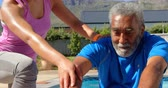 pool deck : Front view of mixed-race personal trainer exercising with determined senior black man in backyard. She is instructing him in the sunshine 4k