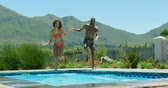 boxer : Front view of young black couple jumping in the swimming pool. They are smiling and having fun 4k