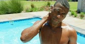 filmagens : Front view of young black man standing in the swimming pool at resort. He is smiling and looking away 4k